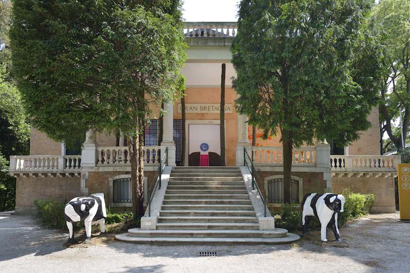 Two concrete cows at the foot of the steps of the British Pavilion act as temple guardians for the brilliant, jam packed with ideas, exhibition: A Clockwork Jerusalem. Photo copyright Cristiano Corte for the British Council © Cristiano Corte, All Rights Reserved.